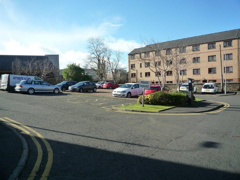 Grand parking privé à l'arrière de l'immeuble. Gratuit pour les clients à utiliser 24/7 avec de vastes espaces.
