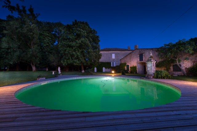 mansão com piscina e grandes paredes de jardim fechado