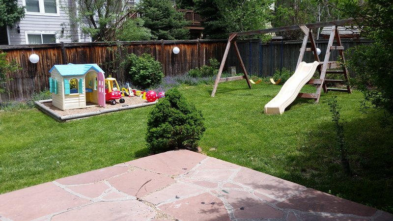 Privacy-Fenced Backyard with Swing Set, Play Area, Patio Table/Umbrella and Charcoal Kettle Grill.