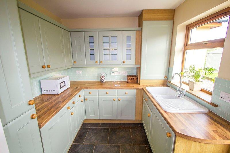 Ruime bijkeuken grenzend aan de keuken met 2 koel-vriescombinatie, magnetron, wasmachine en droger