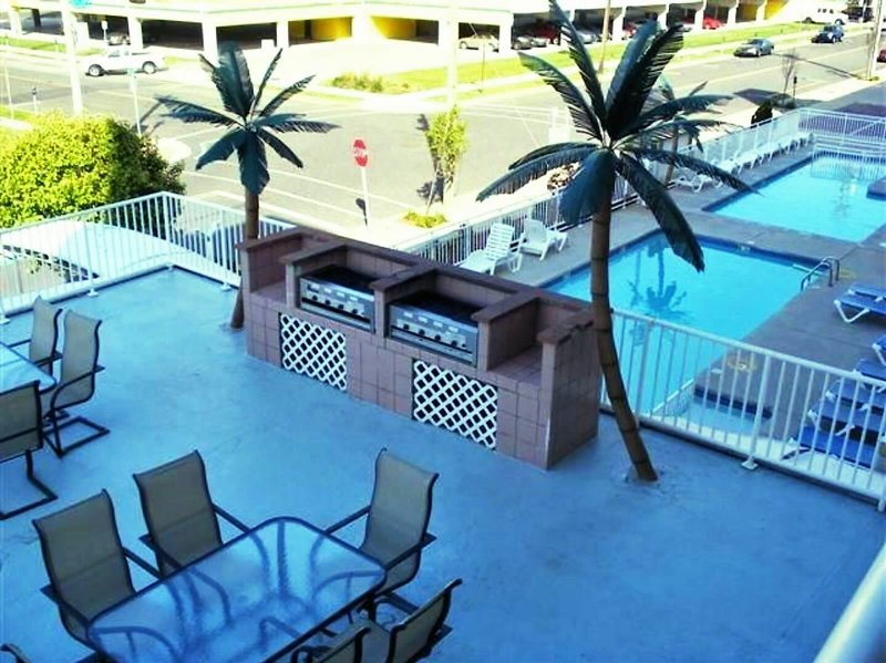 Patio with BBQ grills, overlooking the heated pools!