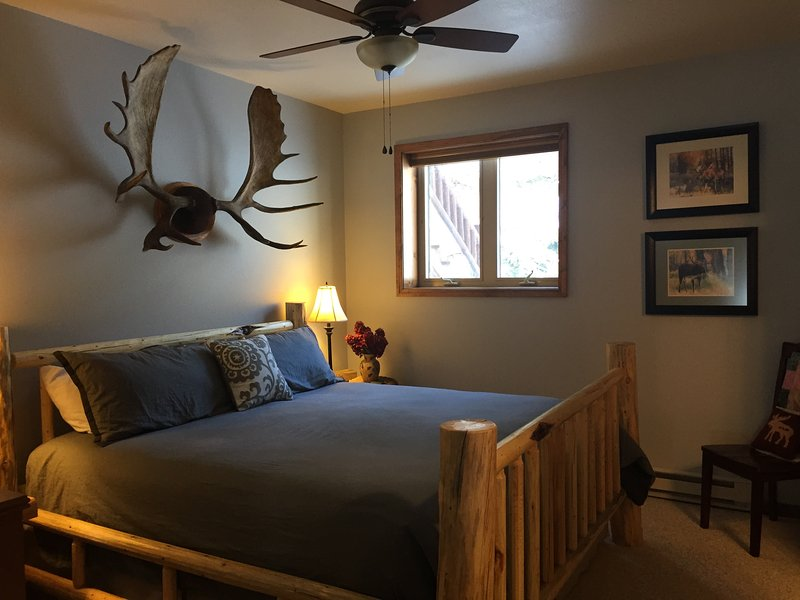 Cozy King log Bed decorated with local photographs and art including Moose Antlers.