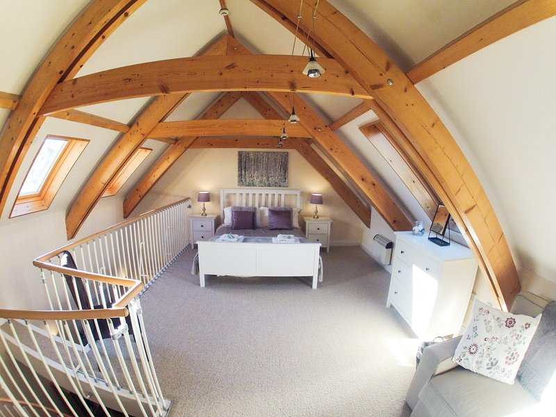 Spacious beamed mezzanine bedroom with kingsize bed and quality comfy sofabed