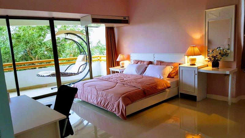 Mestre quarto com cama king size abrir a porta de vidro para a varanda com balanço cama para fora do lado.