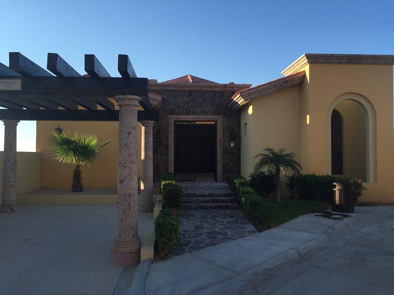 Elevación frontal de la Villa Montecristo: estacionamiento para 1 auto, patio pequeño, entrada con fuente.
