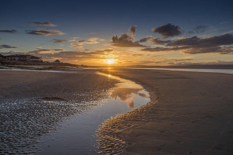 Aproveite o pôr do sol fabulosos com um passeio romântico ao longo da praia a oeste.