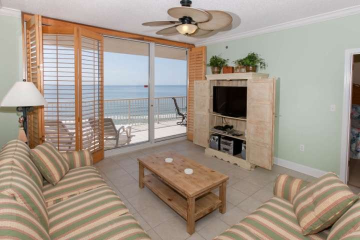 Living room with flat screen TV/DVD and sliding glass doors to Gulf-front patio