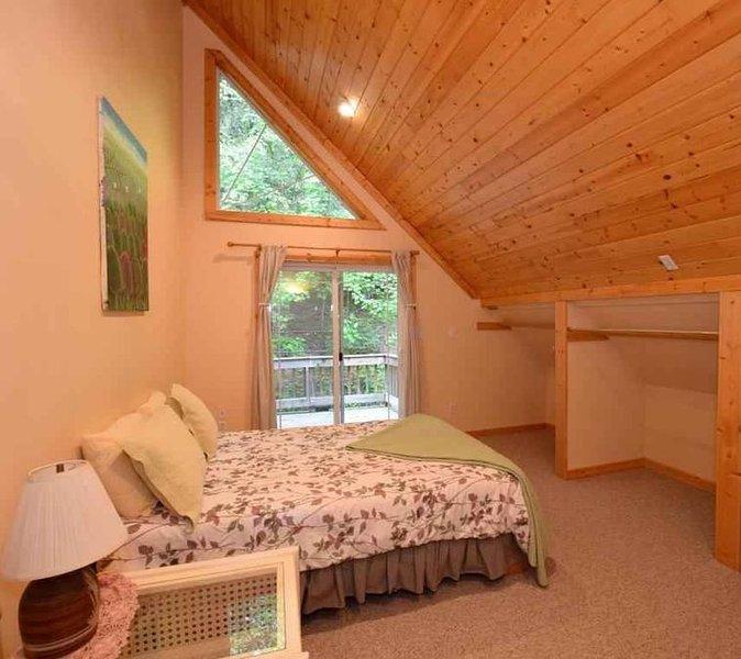 Upper bedroom with wood ceilings