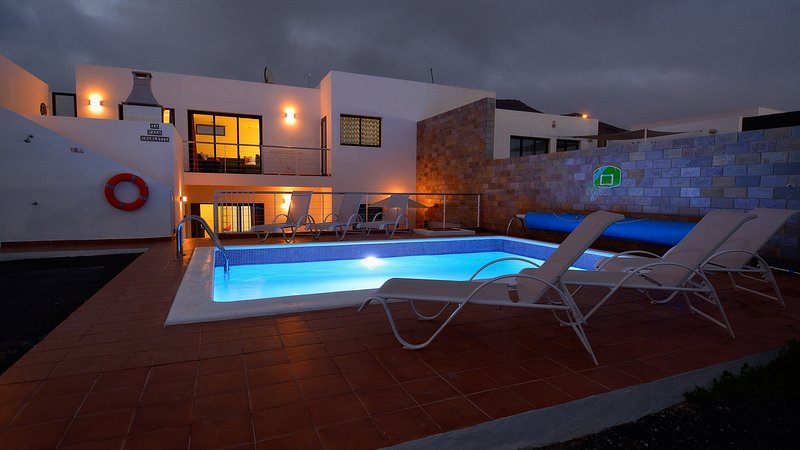 the villa at night with pool lighting