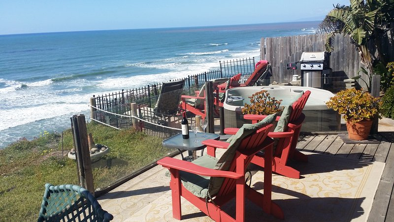 Deck and overlooking the patio with BBQ and hot tub, seating over the Ocean