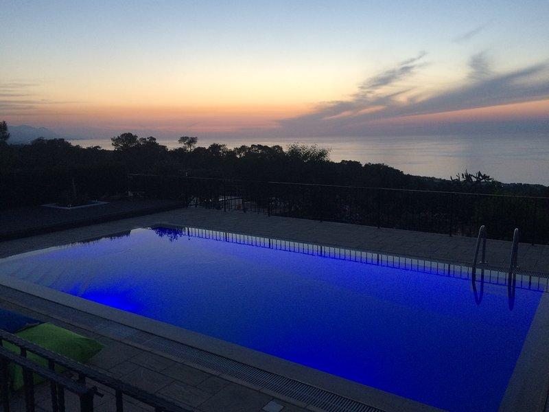 Mágica puesta de sol y piscina con las luces en la noche