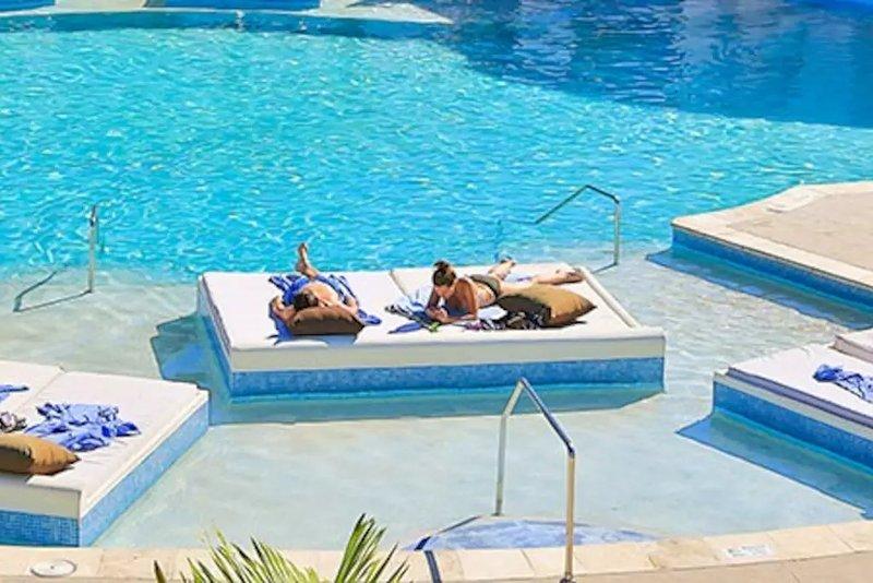 Lotes de relaxar chaises na área da piscina.