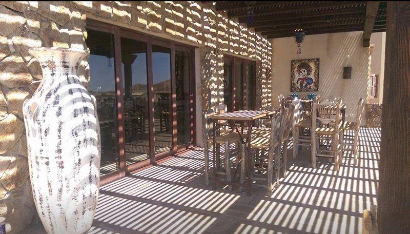 El club de asientos restaurante del patio. Situado en el nivel superior de la casa club. Hermosas vistas del Cabo.