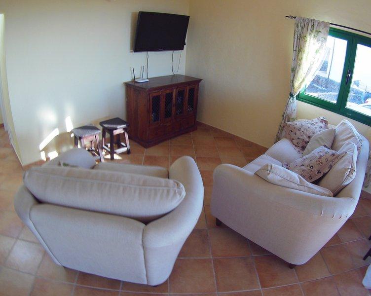 Soggiorno con TV e comode sedie