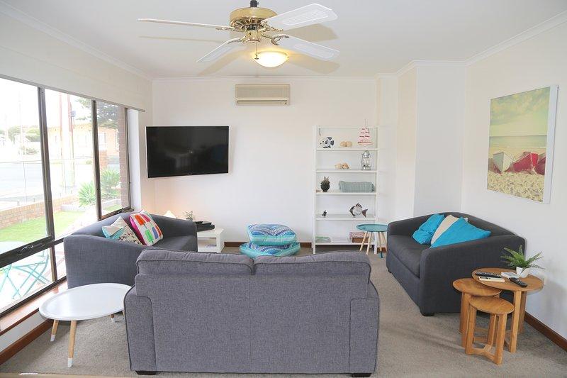 sala de estar con televisión montada en la pared airdcondtioner y ventilador de techo. 2 sofás camas.