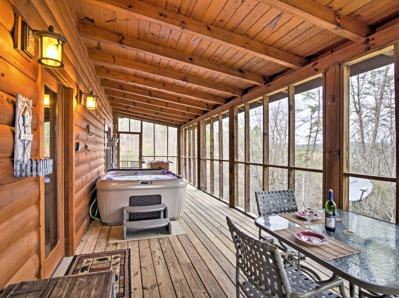 The enclosed porch features a hot tub, a foosball table and patio furniture.