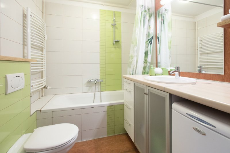 Bathroom with bath tub and shower, toilet, sink and washing machine.
