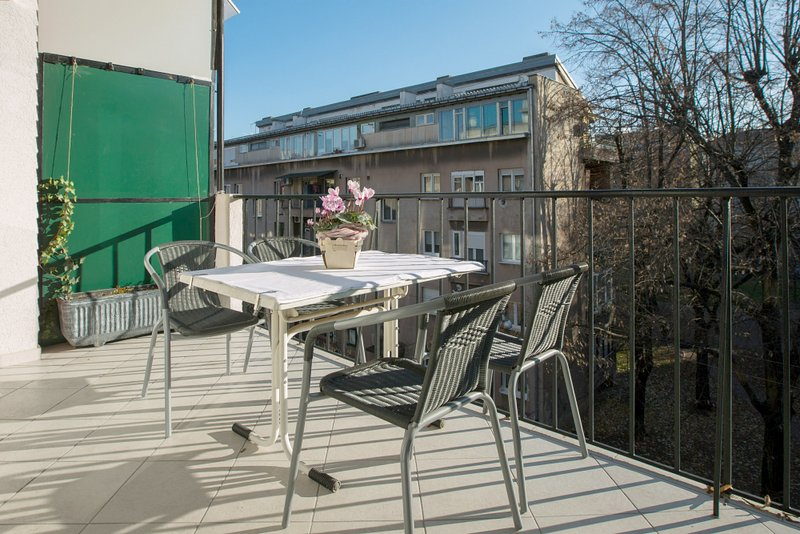 Terrasse ensoleillée avec des fleurs et une table avec 4 chaises.