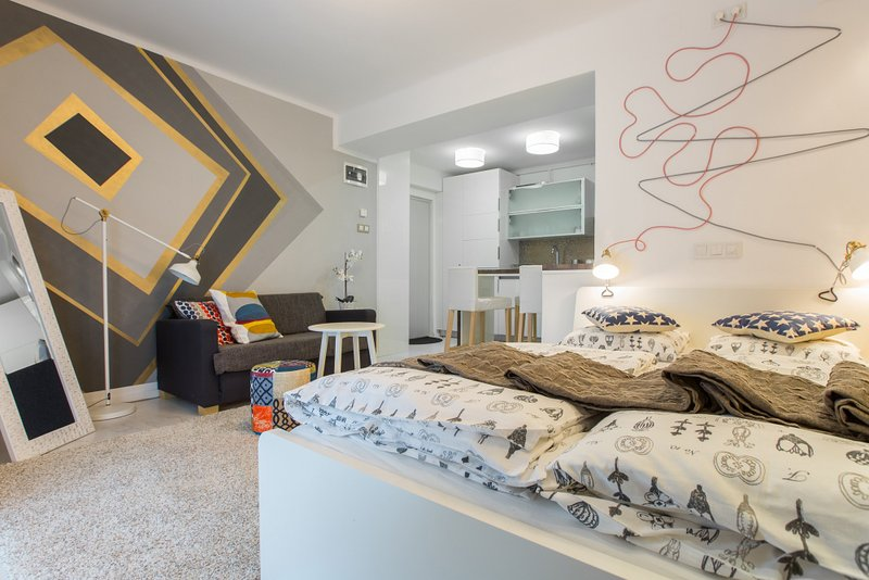 Living room with double bed and sofa bed for child.
