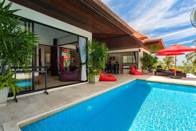 Het terras bij het zwembad met ligbedden en zitzakken