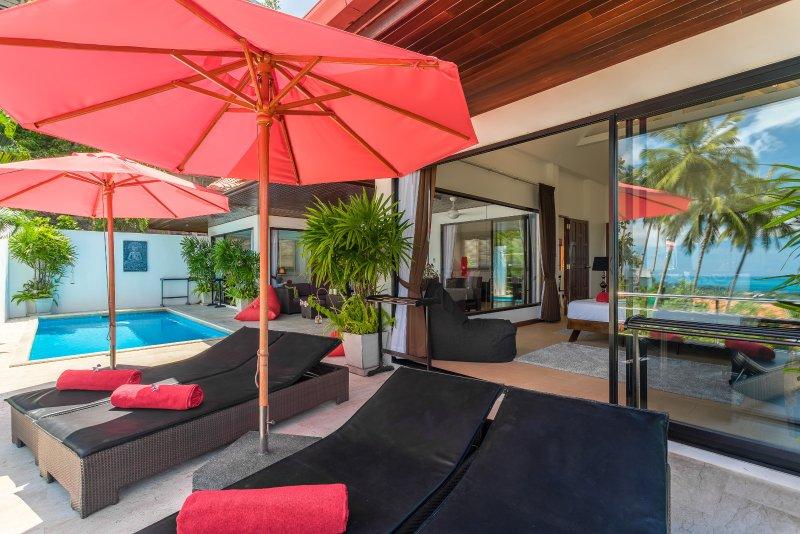Uitzicht op de villa met de reflectie van de palmbomen en de oceaan in de grote patio ramen