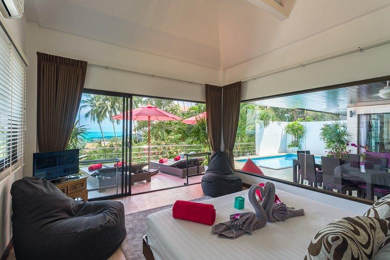 Master en-suite slaapkamer met uitzicht op de oceaan, het zwembad en terras