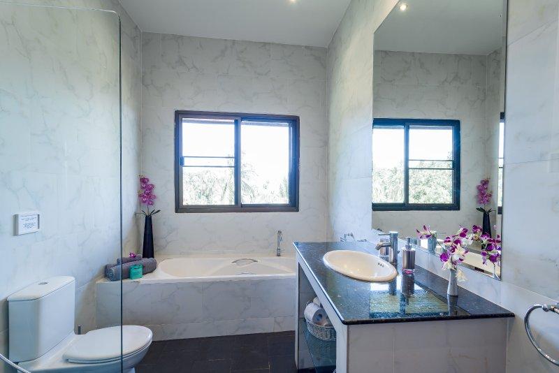 Master-suite badkamer met een ventilator aan de muur
