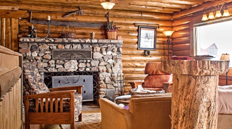 Log walls, large picture windows, and a rock fireplace flow throughout the living area.
