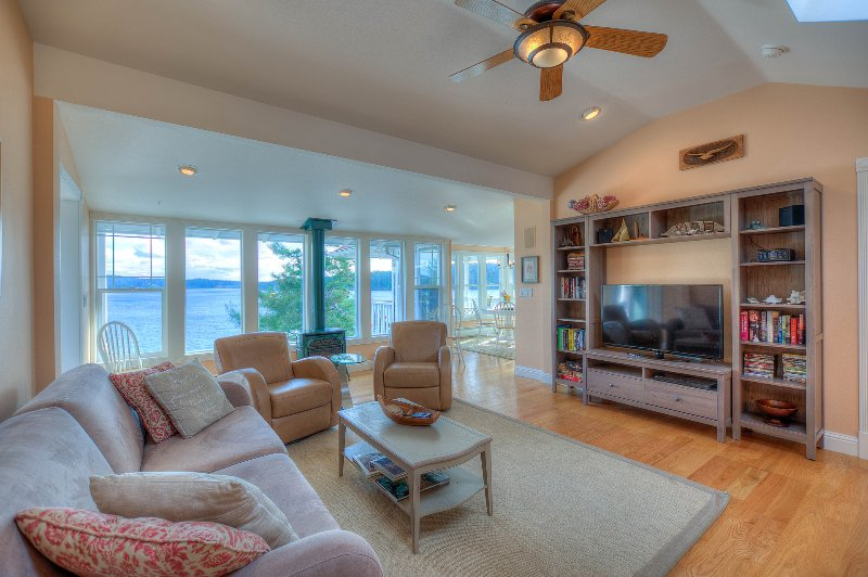 Comfortable living room with wall of windows and propane stove.
