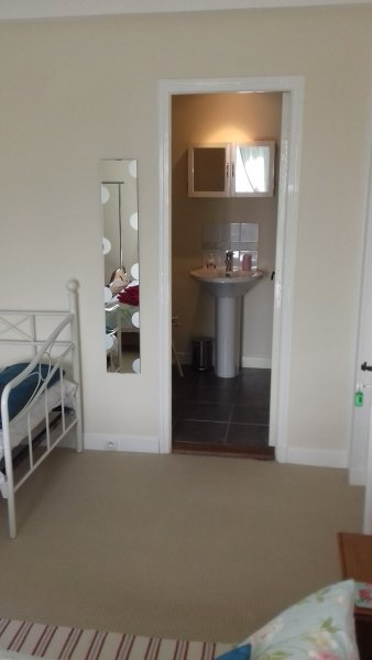 Entrance to the en suite bathroom  with bath and shower over, heated towel rail and a chair
