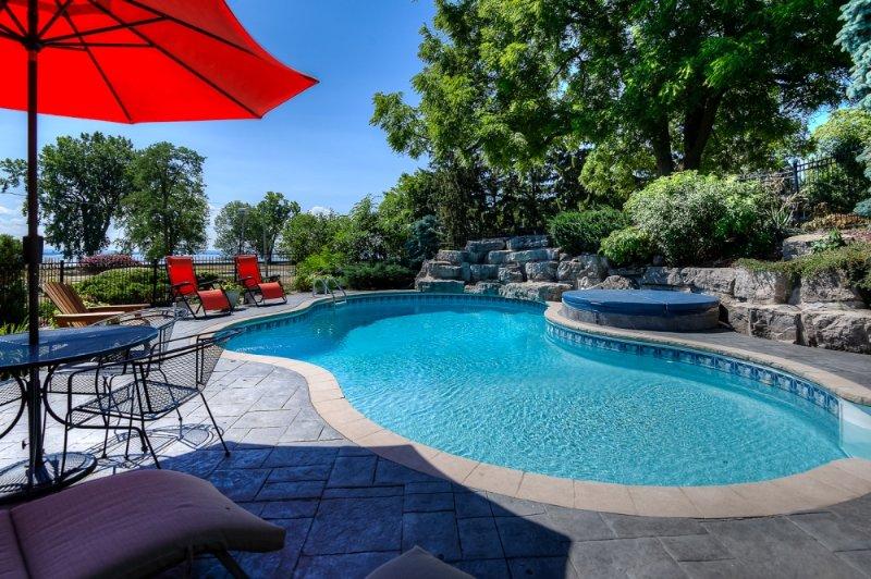 Hermosa piscina enterrada rodeado de jardines y vistas al río