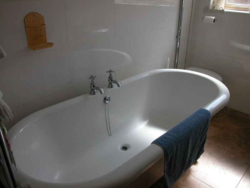 The main bathroom has a roll-top bath