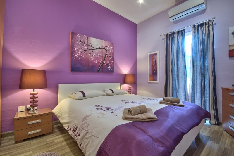 Spacious Main Bedroom with air conditioner and maltese tradition wooden balcony.