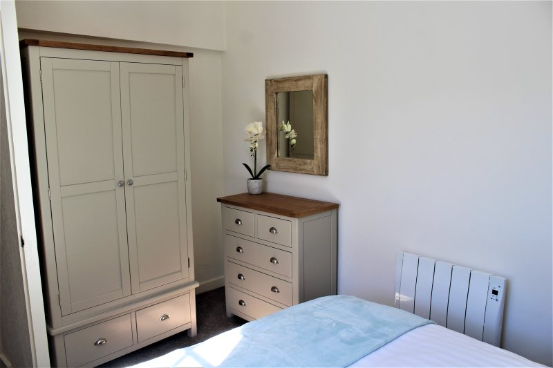 armario dormitorio principal con un montón de perchas, cómoda y secador de pelo
