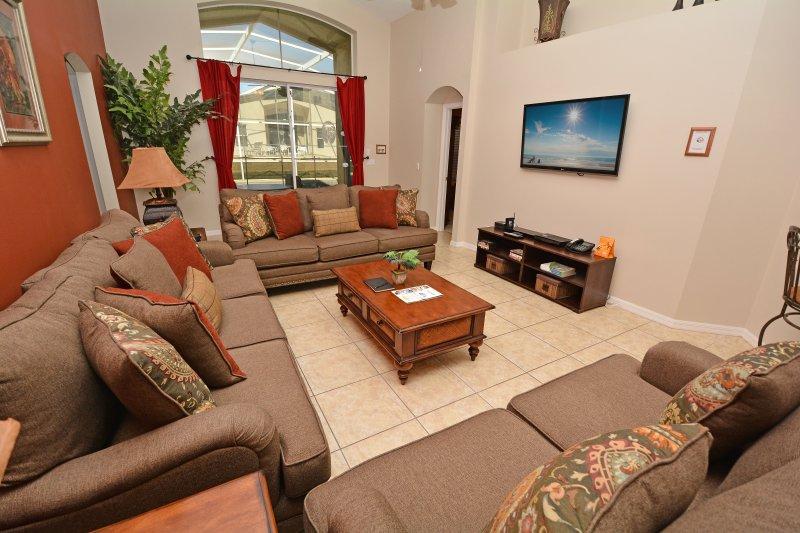Zona de estar familiar con puertas de patio y TV de pantalla plana.