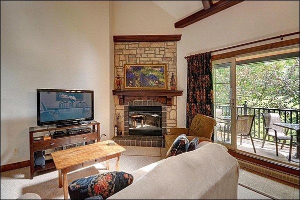 Impresionante sala de estar con chimenea y TV de pantalla plana
