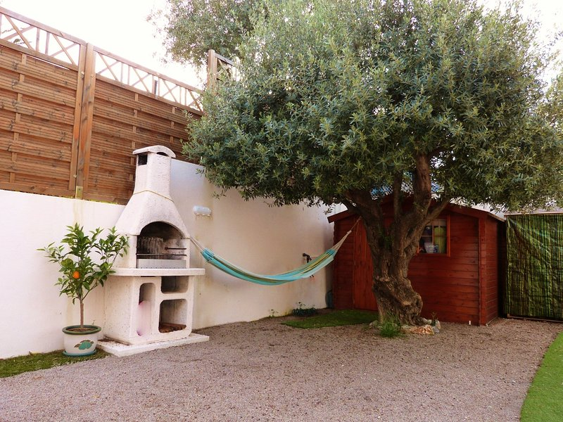 The BBQ area and the hammock under the olive tree ...