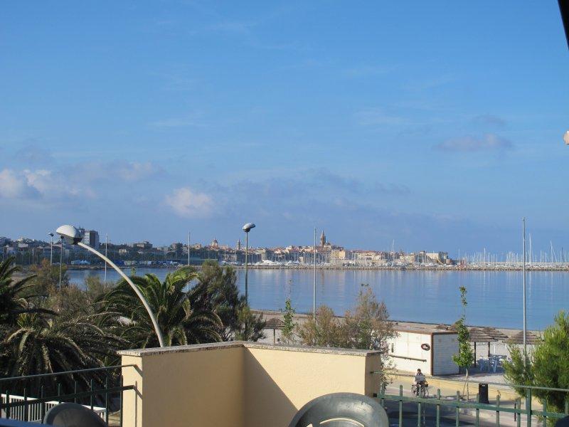 La terraza con vistas a la bahía y la playa debajo de la casa