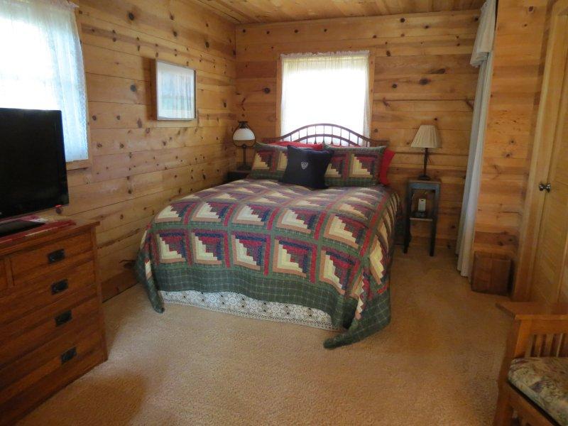 Lit Queen Size confortable surmonté d'un lit de plumes et d'une couette en duvet.