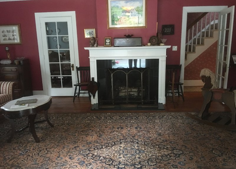 LIVING ROOM WITH FIRE PLACE. PERSIAN RUG. DOORS LEAD TO DINING ROOM AND UPSTAIRS BEDROOMS.