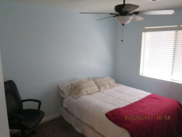Guest room 2 Full bed large closet, ceiling fan and chair.