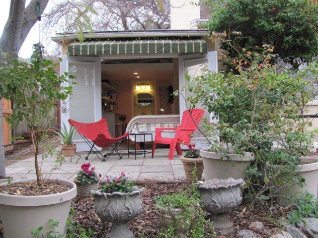 Estudio tiene patio semi-privado que da a la calle bordeada de árboles de pino de abajo y luces de la ciudad