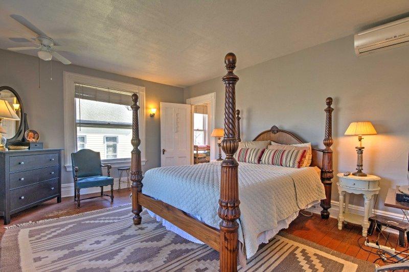 Das geräumige Schlafzimmer verfügt über ein Queen-Size-Bett mit schönen Holzbettpfosten.