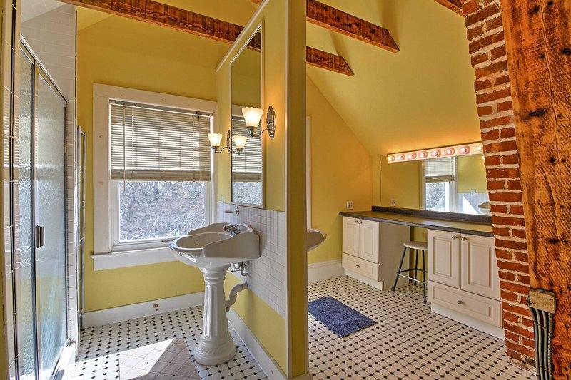 Dieses Badezimmer Merkmale ebenerdiger Dusche, unverputzten Ziegelwänden und schönen Holzbalken.