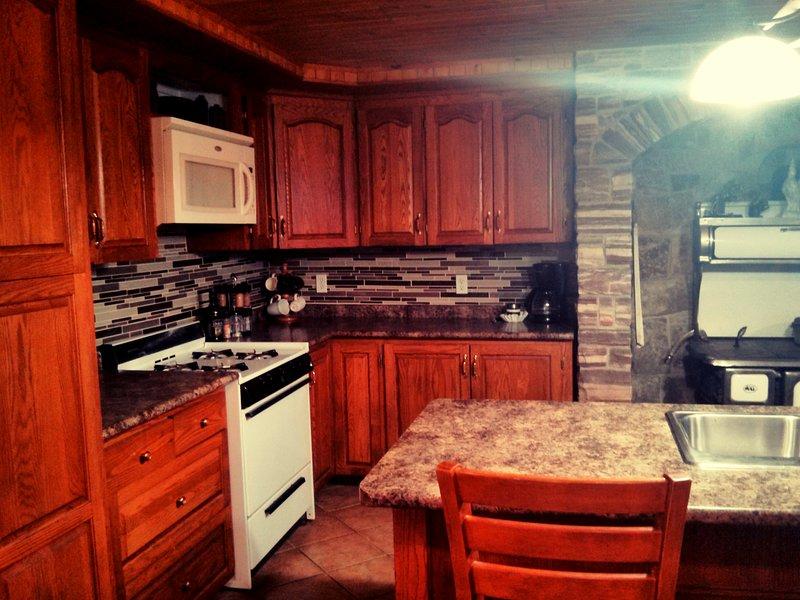 acogedora cocina con horno a gas / estufa.
