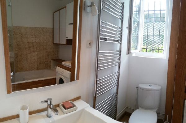The spacious and bright bathroom, oak and stone. Large bathtub, washing machine.