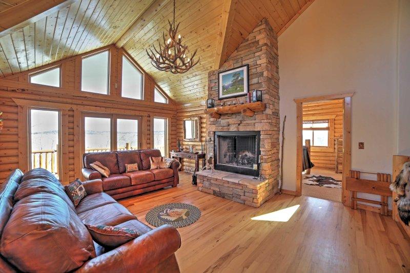 Cozy up neben den Holzkamin auf dem Plüsch Ledercouch und bewundern Sie die umliegende Natur der vom Boden bis zur Decke reichenden Fenster.