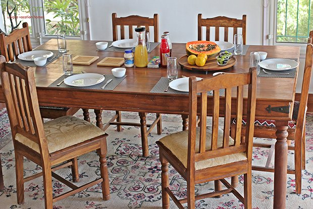Classic wooden farm dining table in teak, seats 6-8 people with large windows with forest views