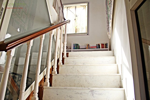 Stairway leading up to bedrooms on first-floor level white marble, with a library on the landing