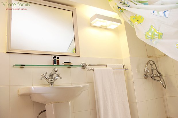 Washroom attached to the attic room done in white tiles with a splash of colour with free amenities